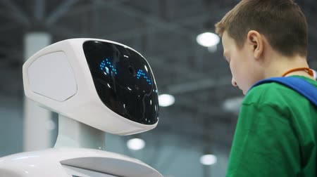 MOSCOW - RUSSIA, 20.03.2018: a white robot interacts with a schoolboy at an exhibition of new technologies. The child gets acquainted with innovations