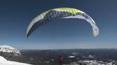 SHEREGESHRUSSIA - 05.04.2018: raises the sail wing of the paraglider. He starts to take off, breaks away from the ground, runs away. Paragliding in winter.