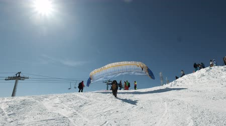 padák : SHEREGESHRUSSIA - 05.04.2018: raises the sail wing of the paraglider. He starts to take off, breaks away from the ground, runs away. Paragliding in winter.