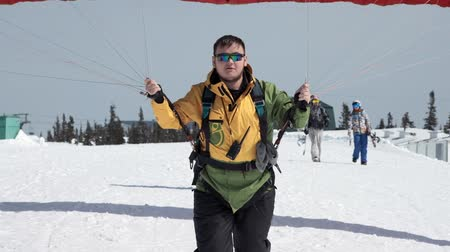 SHEREGESH RUSSIA - 05.04.2018: raises the sail wing of the paraglider. He starts to take off, breaks away from the ground, runs away. Paragliding in winter.