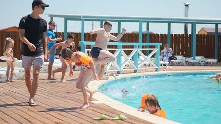 CRIMEARUSSIA - 10.06.2018: Children run and jump into the swimming pool outdoor. Slow motion shoots spray from the water. Children splash water in the pool