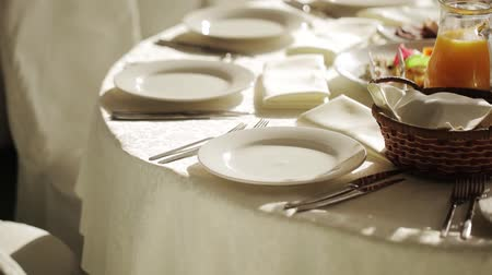 placas : A soft toned image of a table setting with plate, napkin and utensils