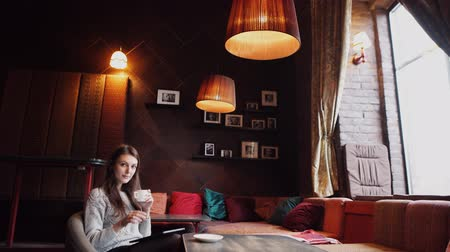 kahve molası : young woman drinking coffee or tea and using tablet computer in a coffee shop Stok Video