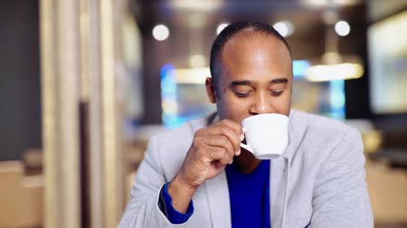 afro americana : African man with  cup of tea, sitting on the desk