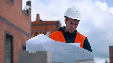 прораб : Architect looking at blueprints in a building site