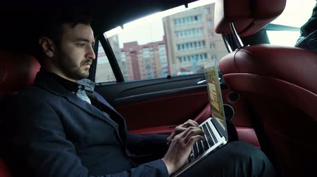 business man : A businessman working in the backseat of a taxi being driven through a financial district