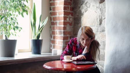 using tablet : Happy young woman drinking coffee tea and using tablet computer in a coffee shop