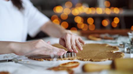 yemek tarifi : Gingerbread cookies preparation recipe, unrecognizable woman hands making dough with rolling pin on white kitchen table. Traditional homemade christmas dessert