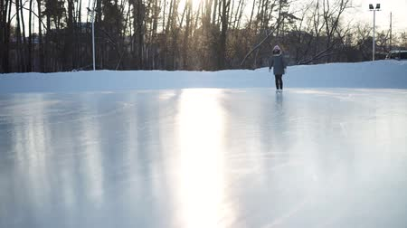 patim : Young woman skating on ice with figure skates outdoors in the snow