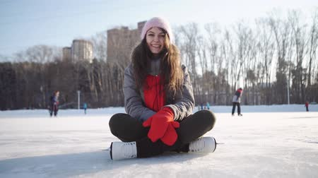 sporty zimowe : young woman fell down on skating rink and holding to her knee