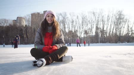 doer : young woman fell down on skating rink and holding to her knee