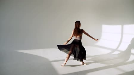 balerína : silhouette of ballerina in classical tutu in the white studio.