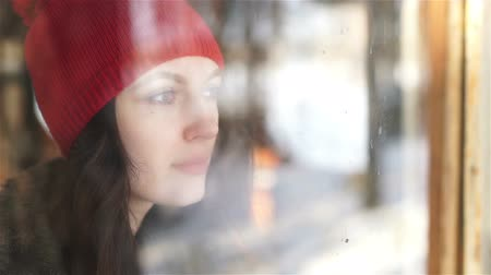 misunderstood : Sad woman looking the rain falling through a window at home or hotel Stock Footage