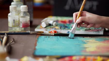 expressionism : artist paints a picture of oil paint brush in hand with palette closeup. Stock Footage