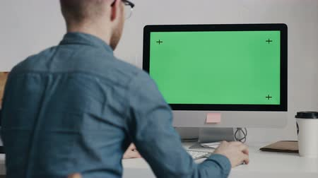 masaüstü : Caucasian worker typing on keyboard and looking at green screen