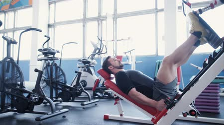 merkez : Man exercising on leg press machine Stok Video