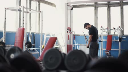levantamento de pesos : Strong man - bodybuilder with dumbbells in a gym, exercising with a barbell Vídeos