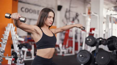 atletismo : Athletic fitness woman pumping up muscles with dumbbells
