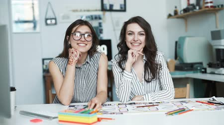 projects : Two women working together at an architect office. look at camera