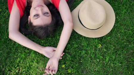 cope space : Relaxing in grass. Top view of beautiful young woman on the green grass Stock Footage