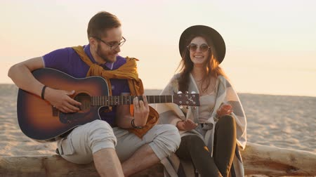 akusztikus : Cute hispanic couple playing guitar serenading on beach in love and embrace