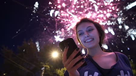 okos telefon : Girl use smart phone , image of firework as a background.