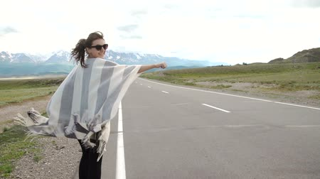 rota : young woman hitch-hiking on a road at the fields