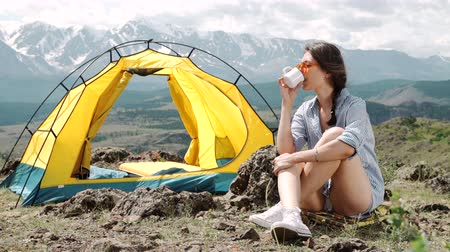 igloo : Girl near bonfire. Travel, tourism, camping - young slim sporty woman tourist brunette at the beautiful nature landscape sitting near the tent by the fire. Girl with drink in mug in her hands
