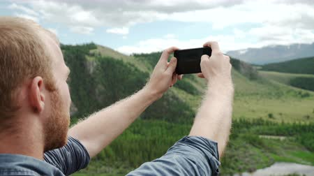 amazonka : Man using smart phone take a photo mountain view Wideo