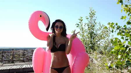 flutuador : Cheerful beautiful young millennial woman holding sprinkled pink inflatable flamingo float in summer. 20s. 1080p Slow Motion.