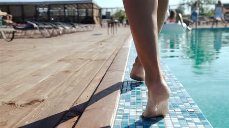 holiday villa : Close up on a womans legs as she walks next to a pool, 20s. 1080p Slow Motion