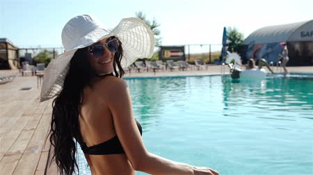bordas : beautiful woman in a hat sitting on the edge of the swimming pool. 20s. 1080p Slow Motion