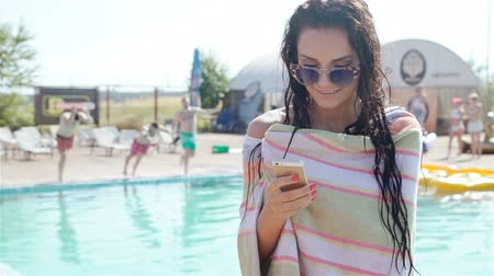 pic : Portrait of beautiful girl taking a mobile phone at the swimming pool. 20s. 1080p Slow Motion