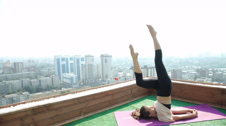 tetőtéri : Yoga on rooftop. Happy young woman stretching on roof with city and mountains view. 20s. 4k Stock mozgókép