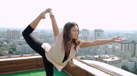 tetőtéri : Yoga on rooftop. Happy young woman stretching on roof with city and mountains view. 20s. 1080p Slow Motion Stock mozgókép