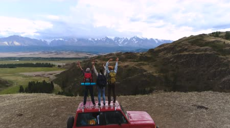vacation : a group of young travelers stands by the car in the background of a mountain landscape 4k slow motion aerial shot 20s 4k