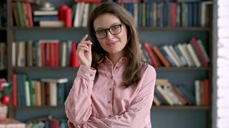 convidar : portrait of lovely young librarian woman standing in library attractive student smiling close up