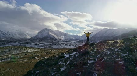 rozjařenost : Young Hiker Reaching The Top Outstretched Arms Success Pose At Sunset In Snowy Mountain Range Aerial Flight Epic Victory Life Gratefulness Religion Concept Dostupné videozáznamy
