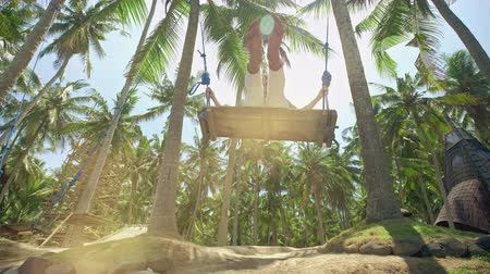 A girl swings on a swing and looks at the sunset on a tropical seashore. Freedom, rest, vacation, travel concept Dostupné videozáznamy