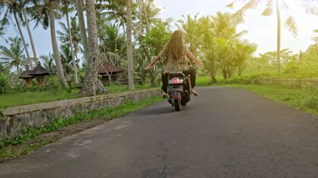 Happy couple tripping by motorcycle on tropical road at sunset time. Outdoor shot of young couple riding motorbike. Man riding on a motorcycle with girlfriend on rural road. Dostupné videozáznamy