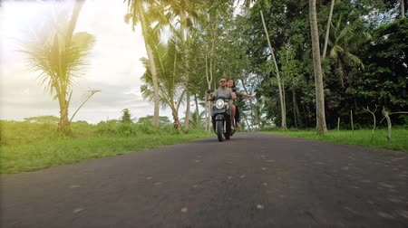 Couple riding their scooter through forest. life style idea concept. Young beautiful couple rides the jungle on a scooter, travel, freedom, happiness, vacation, honeymoon concept