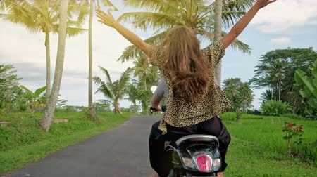 feliz : Happy couple tripping by motorcycle on tropical road at sunset time. Outdoor shot of young couple riding motorbike. Man riding on a motorcycle with girlfriend on rural road. Stock Footage