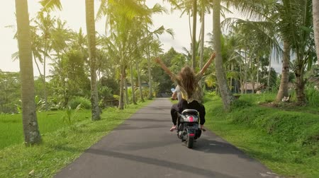 robogó : Couple riding their scooter through forest. life style idea concept. Young beautiful couple rides the jungle on a scooter, travel, freedom, happiness, vacation, honeymoon concept