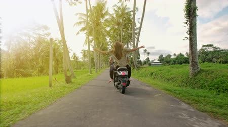 Happy couple tripping by motorcycle on tropical road at sunset time. Outdoor shot of young couple riding motorbike. Man riding on a motorcycle with girlfriend on rural road. Vídeos