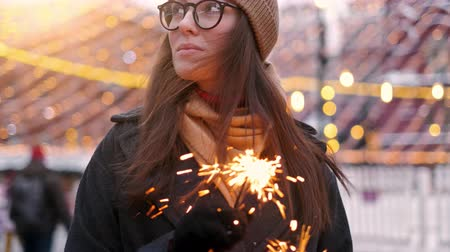Outdoor of young beautiful happy smiling girl holding sparkler, walking on street. Model looking up, wearing stylish winter clothes.
