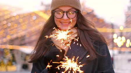 bengália : Outdoor of young beautiful happy smiling girl holding sparkler, walking on street. Model looking up, wearing stylish winter clothes.