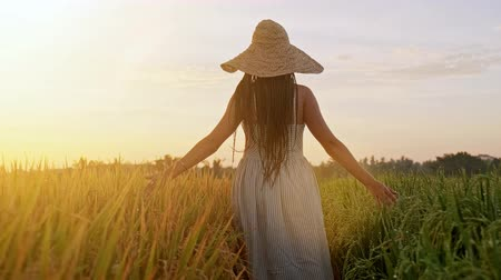 Sensual young woman in white dress enjoying in violet lavender filed at beautiful summer sunset. Young female enjoying nature and sunlight in straw field.
