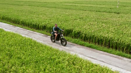 Motorcycle driver riding on a the rice fields. Outdoor shot, countryside landscape. Travel and sport photography. Speed and freedom concept.