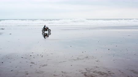 Young handsome hipster man riding modern custom motorcycle racer on the black sand beach near the water. Surfing spot with ocean waves. Vídeos