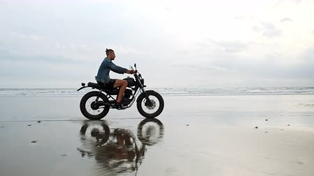 Man in riding motorcycle on beach. vintage motorbike on beach sunset on Bali. Young hipster male enjoying freedom and active lifestyle, having fun on a bikers tour Vídeos